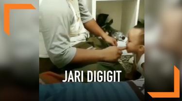 Seorang anak tega menggigit jari sang ayah yang sedang melakukan salat. Aksi ini terekam kamera dan diabadikan oleh sang ibu.