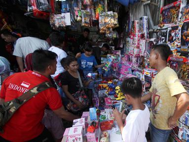 Suasana saat warga membeli mainan di Pasar Gembrong, Jakarta, Selasa (19/6). Libur Lebaran dimanfaatkan sejumlah anak-anak untuk berburu mainan di Pasar Gembrong. (Liputan6.com/Angga Yuniar)