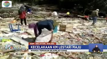Warga Pulau Selayar, mengais barang-barang korban KM Lestari Maju yang terbawa ke pinggir pantai.