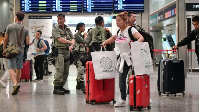 Penumpang melintas saat polisi anti huru-hara berjaga di stasiun Airport Express di Central yang menghubungkan ke Bandara Internasional Chek Lap Kok, Hong Kong (7/9/2019). Pengunjuk rasa pro-demokrasi berencana mengganggu jaringan transportasi ke bandara pada 7 September. (AFP Photo/Anthony Wallace)