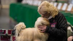 Seorang wanita mencium anjing Lhasa Apso-nya sebelum tampil pada hari kedua pertunjukan anjing Crufts di National Exhibition Centre di Birmingham, Inggris tengah, (9/3). (AFP Photo/Oli Scarff)