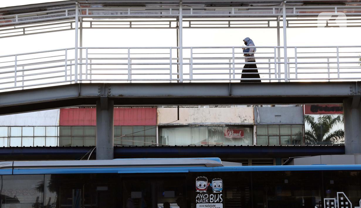 Warga melintas di JPO menuju halte transjakarta Harmoni, Jakarta, Kamis (1/10/2020). Pemberlakuan PSBB II berdampak pada menurunya pengguna transjakarta, selama dua pekan penerapan jumlah pengguna transjakarta tercatat 3.632.047. (Liputan6.com/Helmi Fithriansyah)
