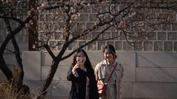 Dua wanita menggunakan ponsel berselfie di istana Changdeokgung di Seoul , Korea Selatan (2/4). Korea Selatan sedang bersiap untuk meluncurkan jaringan seluler 5G pertama di dunia pada 5 April. (AFP Photo/Ed Jones)