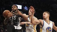 Pemain Warriors, Klay Thompson (tengah) dan Stephen Curry (kanan) menghadang laju pemain  Brooklyn Nets, Trevor Booker pada laga NBA di Barclays Center, (22/12/2016). Warriors menang 117-101.  (Reuters/Nicole Sweet-USA TODAY Sports)