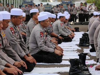 Personel Brimob yang tergabung dalam Pasukan Dzikir Asmaul Husna melakukan salat di depan Gedung MPR/DPR, Senayan, Jakarta, Selasa (24/10). Sebanyak 299 personel dikerahkan untuk menjaga demo menolak Perppu Ormas di gedung DPR. (Liputan6.com/JohanTallo)