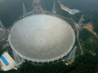 Teleskop Radio terbesar di dunia, Aperture Spherical Telescope atau FAST, terlihat pada hari pertama uji coba di Pingtang, Guizhou, China, Minggu (25/9). Berdiameter 500 meter, teleskop raksasa itu digunakan untuk mendeteksi keberadaan alien. (STR/AFP)