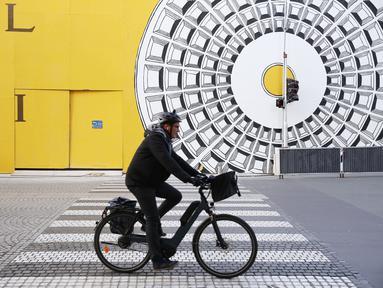 Seorang pria mengendarai sepeda di sebuah jalan di Paris, Prancis, 25 November 2020. Warga Prancis akan menikmati lebih banyak kebebasan dalam melakukan berbagai kegiatan di luar ruangan mulai 28 November 2020.(Xinhua/Gao Jing)