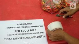 Petugas bersiap menempel pengumuman terkait penggunaan kantong plastik di Pasar Mitra Tani, Jakarta, Selasa (30/6/2020). Pasar Mitra Tani akan melarang penggunaan kantong plastik sekali pakai untuk seluruh vendor dan konsumen pasar mulai Rabu, 1 Juli 2020. (Liputan6.com/Angga Yuniar)