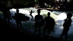 Sejumlah peselancar melihat rekannya menaklukkan ombak buatan saat bermain surfing di sungai 'Eisbach' di taman English Garden di Munich, Jerman (24/6/2019). Sungai Eisbach dipakai sebagai tempat berselancar sejak 1972 namun baru secara resmi diperbolehkan pada 2010. (AP Photo/Matthias Schrader)
