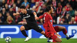 Gelandang Salzburg, Hwang Hee-Chan, mengocek bek Liverpool, Virgil Van Dijk pada laga Liga Champions di Stadion Anfield, Liverpool, Rabu (2/10). Liverpool menang 4-3 atas Salzburg. (AFP/Paul Ellis)