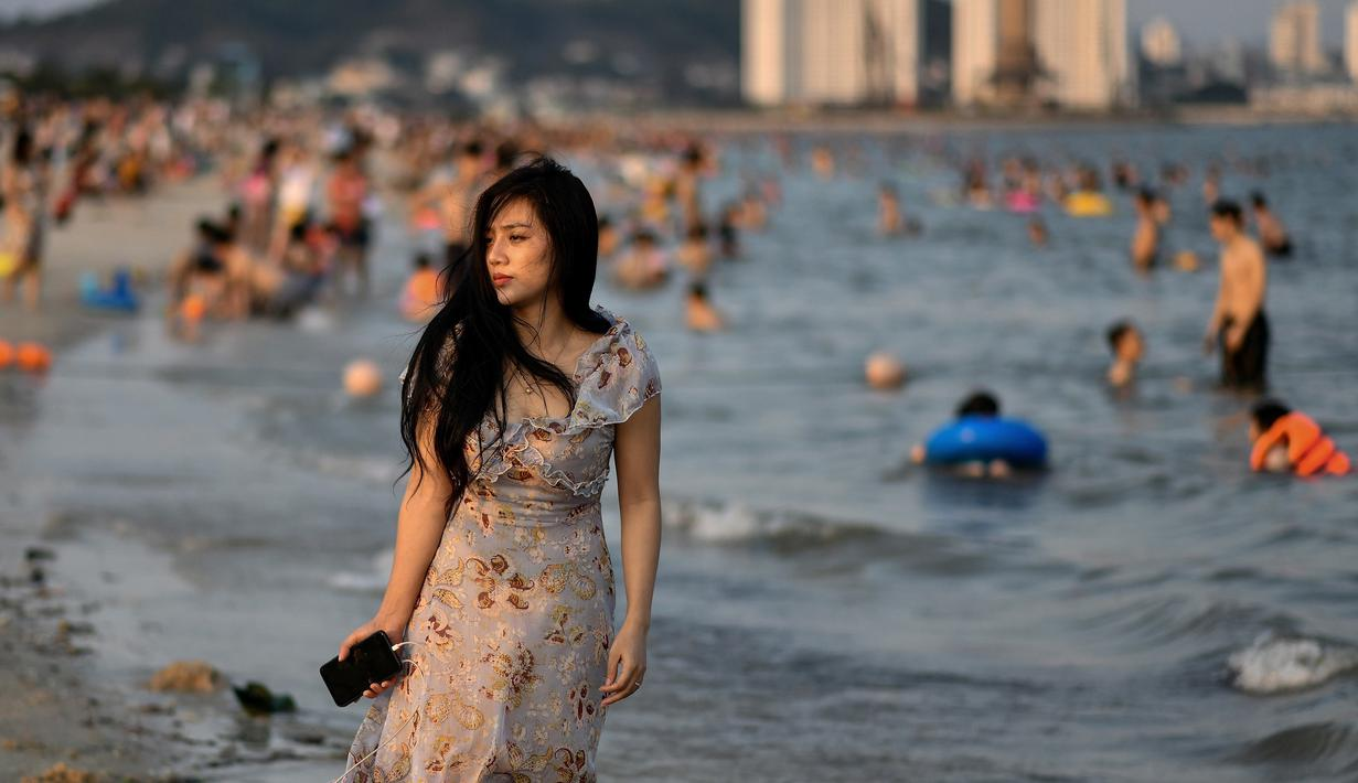 Seorang wanita berjalan di sepanjang pantai Bai Chay di kota Ha Long provinsi timur laut Quang Ninh (16/5/2020). Seiring dengan meredanya virus corona dan otoritas setempat melonggarkan pembatasan perjalanan, pantai Bai Chay kembali didatangi ratusan wisatawan. (AFP/Manan Vatsyayana)