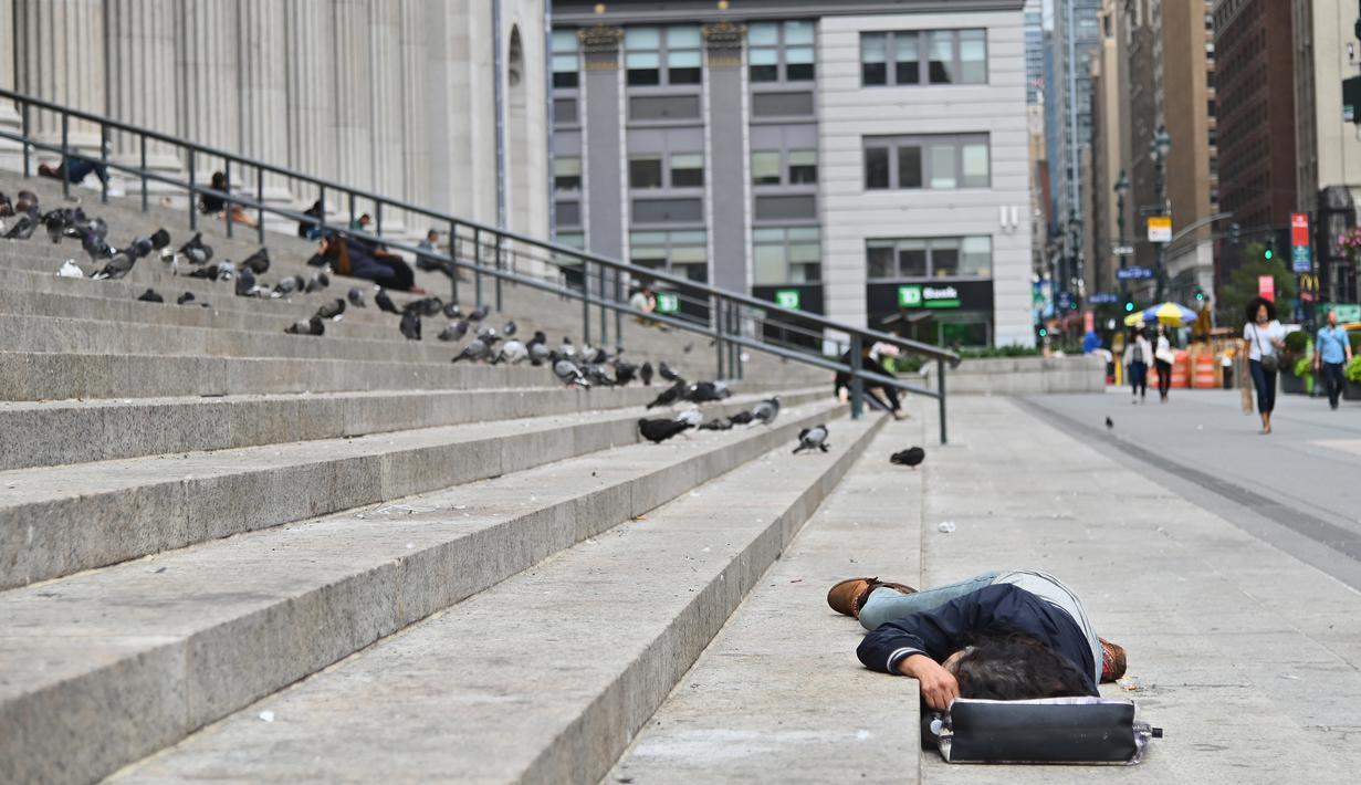 Seseorang tidur di dekat Penn Station di Madison Square Gardens, New York City pada Kamis (17/9/2020). Sejak pandemi virus corona, para tunawisma kini lebih terlihat seiring banyaknya penutupan banyak tempat penampungan karena alasan kesehatan. (Angela Weiss / AFP)