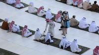 Petugas membagikan air zam-zam kepada para jemaah yang melaksanakan salat Idul Fitri di Masjidil Haram, Mekah, Arab Saudi, Minggu (24/5/2020). Salat Idul Fitri tetap digelar di Masjidil Haram dan Masjid Nabawi namun dengan jemaah terbatas. (AFP)