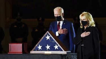 Presiden AS Joe Biden dan Ibu Negara Jill Biden memberi penghormatan kepada polisi yang tewas dalam kerusuhan Capitol Hill Brian Sicknick di tengah Capitol Rotunda, Washington, Selasa (2/2/2021). Abu jenazah Brian Sicknick dihadirkan dalam upacara ini. (Erin Schaff/The New York Times via AP, Pool)