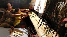 Dalang Ki Purbo Asmoro mengajar siswa belajar mendalang pada pagelaran wayang kulit di Jakarta Intercultural School (JIS) Elementary, Jakarta, Kamis (2/11). Pagelaran ini merupakan bagian dari JIS cultural week. (Liputan6.com/Fery Pradolo)