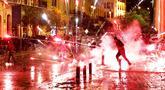 Demonstran antipemerintah melemparkan petasan ke arah polisi antihuru-hara saat demonstrasi menentang pemerintahan baru di dekat Parliament Square, Beirut, Lebanon, Rabu (22/1/2020). Demonstrasi dan kekerasan terus berlanjut kendati Lebanon telah mengumumkan kabinet baru. (AP Photo/Hussein Malla)
