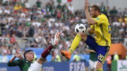 Pemain Meksiko, Edson Alvarez (kiri) menghalau bola dari kejaran pemain Swedia, Ola Toivonen pada laga grup F Piala Dunia 2018 di Yekaterinburg Arena, Yekaterinburg, Rusia, (27/6/2018).  Swedia menang telak 3-0 atas Meksiko. (AP/Martin Meissner)