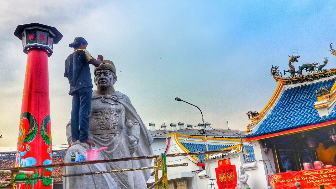 Seorang pekerja sedang membersihkan dan merapikan patung Laksamana Cheng Hoo di Kelenteng Tay Kak Sie. (foto : Liputan6.com/vega/edhie prayitno ige)