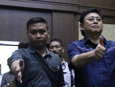 Advokat Lucas (kanan) mengacungkan jempol jelang sidang dakwaan di Pengadilan Tipikor, Jakarta, Rabu (7/11). Lucas didakwa menghalangi proses penyidikan KPK terhadap tersangka mantan petinggi Lippo Group, Eddy Sindoro. (Liputan6.com/Helmi Fithriansyah)
