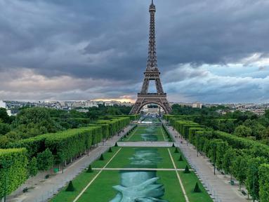 """Foto udara dari lukisan raksasa """"Beyond Walls"""" karya seniman jalanan Prancis, Saype, yang terbentang di halaman Champs de Mars, depan Menara Eiffel di Paris, 13 Juni 2019. Karya berukuran 600 meter itu bentuk dukungan kepada organisasi amal penyelamat migran, SOS Mediterranee. (Eric FEFERBERG/AFP)"""