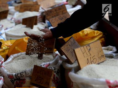 Pedagang melihat beras dagangannya di Pasar Induk Cipinang, Jakarta, Senin (25/9). Pedagang beras Cipinang sudah menerapkan dan menyediakan beras medium dan beras premium sesuai harga eceran tertinggi (HET). (Liputan6.com/Angga Yuniar)
