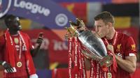 Pemain Liverpool James Milner mencium trofi Liga Inggris usai bertanding melawan Chelsea di Anfield Stadium, Liverpool, Inggris, Rabu (22/7/2020). Penyerahan trofi Liga Inggris kepada Liverpool digelar tanpa penonton karena pandemi COVID-19.  (Paul Ellis, Pool via AP)