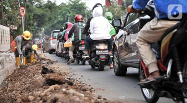 Laju kendaraan tersendat saat melintasi proyek revitalisasi trotoar di Jalan Tebet Raya, Jakarta, Selasa (5/11/2019). Adanya proyek revitalisasi trotoar di sepanjang Jalan Tebet Raya mengakibatkan kemacetan di kawasan tersebut semakin parah, terlebih saat jam sibuk. (merdeka.com/Iqbal Nugroho)