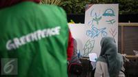 Seorang pengunjung mengikuti aksi melukis di kanvas disela kegiatan Car free Day (CFD) di kawasan Bundaran HI, Jakarta, Minggu (12/2). Aksi yang digelar oleh Greenpeace itu untuk mengenalkan masyarakat tentang sadar polusi. (Liputan6.com/Faizal Fanani)