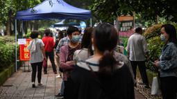 Warga mengenakan masker menunggu dalam barisan untuk tes virus corona di lingkungan di Wuhan, provinsi Hubei, China, Jumat (15/5/2020). Pihak berwenang Kota Wuhan menggelar tes massal terhadap 11 juta warganya untuk mencegah gelombang kedua pandemi Covid-19. (Hector RETAMAL/AFP)