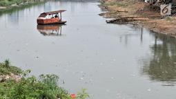 Perahu getek melintasi aliran Kanal Banjir Barat yang tengah dipenuhi sampah, Jakarta, Senin (22/10). Sampah yang memenuhi aliran kanal pencegah banjir tersebut didominasi plastik dan limbah rumah tangga. (Merdeka.com/Iqbal Nugroho)