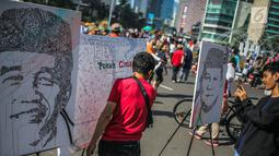 Masyarakat menandatangani dilukisan capres 01 dan 02  yang bertema ' Pemilu Penuh Cinta'  saat Car Free day di kawasan Bundaran HI, Jakarta, MInggu (14/4). Kampanye tersebut untuk mengajak masyarakat untuk berpartisipasi dalam Pemilu secara Damai. (Liputan6.com/Faizal Fanani)