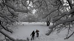 Dua wanita berjalan berjalan di di tengah-tengah pohon yang tertutup salju setelah salju yang turun di malam hari di Ankara, Turki (26/12). (AFP Photo/Adem Altan)