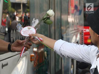 Relawan Jokowi saat membagikan bunga mawar di Kawasan Sarinah, Jakarta, Minggu (29/9/2019). Aksi bagi bunga tersebut merupakan aksi damai kami bersama Jokowi. (Liputan6.com/Angga Yuniar)