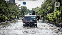Kendaraan bermotor melintasi jalan yang tergenang air rob (banjir pasang air laut) di Kawasan Pasar Ikan Muara Baru, Jakarta, Kamis (4/6/2020). Banjir rob di Pelabuhan Muara Baru tersebut terjadi akibat cuaca ekstrem serta pasangnya air laut. (Liputan6.com/Faizal Fanani)