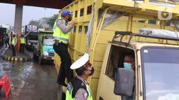 Polisi melakukan pemeriksaan dengan menaiki badan truk saat penyekatan larangan mudik lebaran di gerbang tol Cikupa, Kabupaten Tangerang, Banten, Kamis (6/5/2021). Penyekatan dilakukan seiring telah diberlakukan larangan mudik Lebaran mulai dari 6 hingga 17 Mei 2021.  (Liputan6.com/Angga Yuniar)