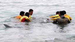 Petugas penyelamat membantu paus sperma terluka yang terdampar di perairan San Bartolo, Peru, Selasa (20/8/2019). Dokter hewan ORCA merawat dan kemudian mengembalikannya ke laut dengan bantuan personel penyelamat dan peselancar. (AP Photo/Martin Mejia)