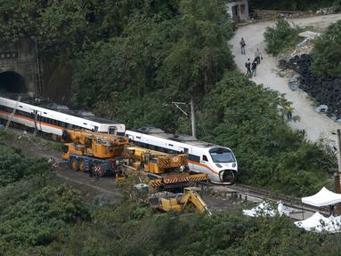 Petugas penyelamat memindahkan bagian dari kereta yang tergelincir dekat Ngarai Taroko di Hualien, Taiwan, Sabtu (3/4/2021). Badan Pemadam Kebakaran Nasional Taiwan melaporkan korban jiwa tabrakan kereta di Hualien bertambah hingga 50 orang dan melukai 66 lainnya. (AP Photo/Chiang Ying-ying)