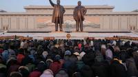 Warga Korea Utara membungkuk di hadapan patung Kim Il-sung dan Kim Jong-il di Pyongyang, dalam perayaan HUT mendiang ayah Kim Jong-un itu pada 16 Februari 2019 (AFP PHOTO)
