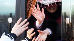 Pemain tim hoki wanita Korea Utara melambaikan tangan pada rekannya asal Korea Selatan saat akan kembali ke negaranya usai mengikuti Olimpiade Pyeongchang di Olympic Village, Gangneung, Korea Selatan, Senin (26/2). (Yun Dong-jin/Yonhap via AP)