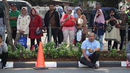 Sejumlah warga berdiri di sisi jalan TMP Kalibata untuk melihat prosesi pemakaman Presiden RI ke-3 BJ Habibie, Jakarta, Kamis (12/9/2019). BJ Habibie meninggal dunia pada Rabu (11/9/2019) pukul 18.05 WIB di usia 83 tahun. (Liputan6.com/Helmi Fithriansyah)