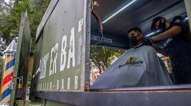 Seorang tukang cukur memotong rambut pelanggan di mobil van atau truck yang diubah menjadi barbershop di sebuah jalan di tengah pandemi virus corona COVID-19, di Mexico City, pada Minggu (6/9/2020). (Photo by CLAUDIO CRUZ / AFP)