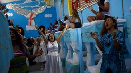 Narapidana perempuan mengenakan kostum dalam acara tahunan menjelang  natal di Penjara Nelson Hungria, Rio de Janeiro, Kamis (13/12). Para tahanan juga menyanyikan lagu religi dan memainkan drama perjalanan hidup Yesus. (AP/Silvia Izquierdo)