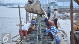 Sejumlah pekerja menyelesaikan proyek pembangunan tanggul di Pantai Muara Baru, Jakarta, Rabu (2/12). Pembangun proyek ini dilakukan di garis bibir pantai sepanjang 32 kilometer. (Liputan6.com/Gempur M Surya)