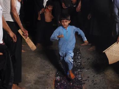 Seorang anak muslim Syiah Pakistan berlari di atas bara api saat peringatan Hari Asyura di Lahore, Rabu (19/9). Hari Asyura diperingati atas kemartiran Imam Hussain, cucu Nabi Muhammad. (ARIF ALI/AFP)