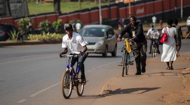 Sejumlah warga menaiki sepeda di sebuah ruas jalan di Kampala, ibu kota Uganda (30/6/2020). Warga Uganda kini beralih menggunakan sepeda sebagai sarana transportasi yang mendukung di tengah pandemi COVID-19. (Xinhua/Hajarah Nalwadda)