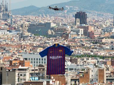 Sebuah drone menerbangkan jersey terbaru milik Barcelona untuk musim 2018/2019 saat diperkenalkan kepada publik di Montjuic Swimming Pool, 19 Mei 2018. Motif seragam Blaugrana sendiri masih menggunakan warna andalannya, merah dan biru. (AFP/Josep LAGO)