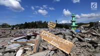 Sebuah papan dengan pesan Kami Rindu Rumah Kami dipasang pasca gempa bumi dan tsunami di pinggir Jalan Trans Sulawesi, Palu, Sulawesi Tengah, Kamis (4/10). (Liputan6.com/Fery Pradolo)
