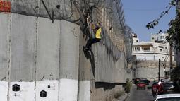 Seorang pria Palestina memanjat pagar perbatasan yang memisahkan Tepi Barat dengan Yerusalem di Distrik Beit Hanina, Yerusalem, Senin (7/10/2019). Banyak warga Palestina dari Tepi Barat menyeberang secara ilegal ke Israel setiap hari untuk mencari pekerjaan. (AHMAD GHARABLI/AFP)