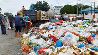 Petugas kebersihan mengangkut tumpukan sampah di Pekanbaru dengan fasilitas operasional terbatas. (Liputan6.com/M Syukur)