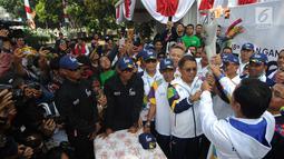 Wali Kota Bogor, Bima Arya Sugiarto menyerahkan obor kepada Menkominfo Rudiantra saat kirab obor Asian Games 2018 di Jawa Barat, Selasa (14/8). Rudiantara menjadi orang pertama pembawa obor dengan berlari sepanjang 500 meter. (Merdeka.com/Arie Basuki)
